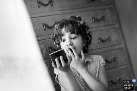 Trapini wedding photographer created this black and white image of the flower girl checking her reflection in a compact mirror