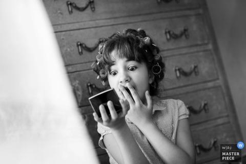 Trapini-trouwfotograaf heeft dit zwart-wit beeld gemaakt van het bloemenmeisje dat haar reflectie in een compacte spiegel controleert