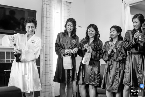 Los Angeles wedding photographer created this black and white image of a bride and her bridal party drinking champagne in their robes