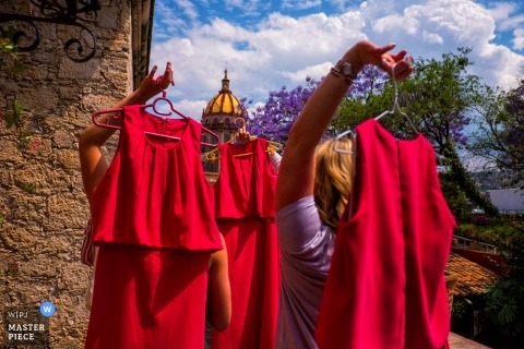 San Diego wedding photographer created this picture of bridesmaids carrying their red dresses on a sunny day.