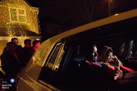 倫敦婚禮攝影師通過夜間騎馬的新娘和新郎的豪華轎車的窗口捕獲了這個圖像