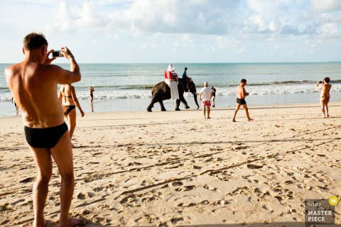 Phuket wedding photographer captured this image of a groom riding an elephant across a sunny beach while beach goers watch and take photos