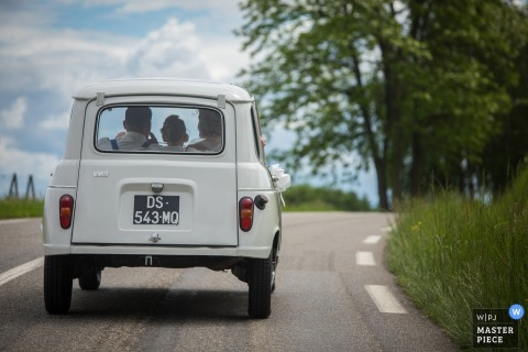 Haut-Rhin wedding photographer captured this image of a bride and groom driving along a rural road on a sunny day