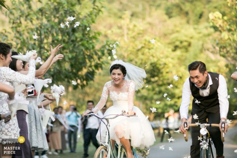 London wedding photographer captured this picture of a bride and groom riding bikes on a sunny day while wedding guests shower them in flower petals