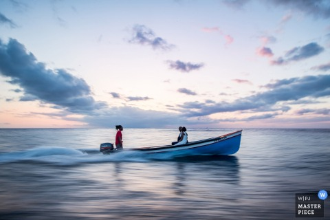 Miami wedding photographer captured this image of a bride and groom riding in a small boat at sunset in calm waters