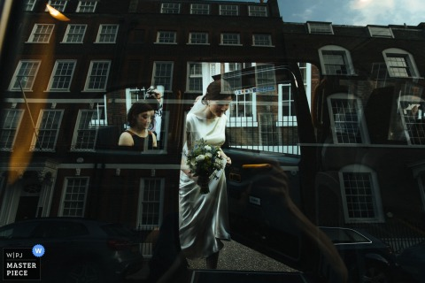 London wedding photographer created this artistic image of a bride stepping out of a car in the sunshine