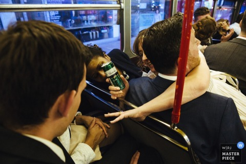 London wedding photographer captured this image of a bride sitting on her grooms lap and drinking a beer while riding on a bus with other members of her wedding party