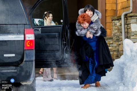 Lake Tahoe wedding photographer created this humorous image of a bridal party member being carried through the snow to protect her dress