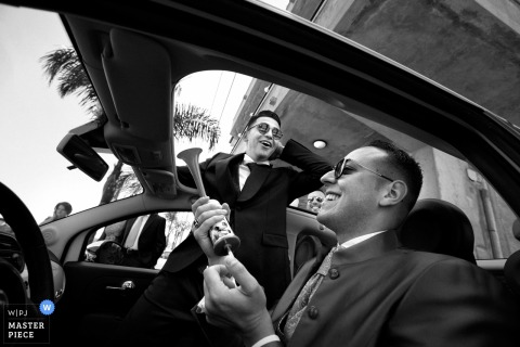 Calabria wedding photographer captured this humorous black and white image of  the groom and groomsmen in the car.