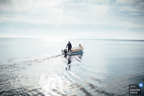 Lazio wedding photographer captured this image of a bride and groom in a boat on a sunny day