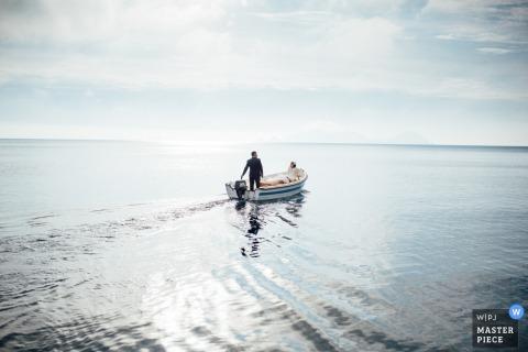 Het huwelijksfotograaf van Lazio ving dit beeld van een bruid en een bruidegom in een boot op een zonnige dag