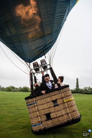 San Francisco wedding photographer captured this image of a bride and groom taking off in a hot air balloon on a cloudy day