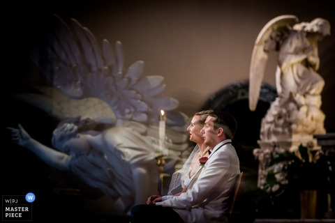 Chicago wedding photographer captured this image of a bride and groom in the mirror with angel statues behind them