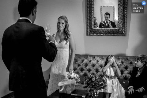 利馬婚禮攝影師創造性地使用鏡子捕捉新郎的反射,敬酒他的新娘,而兩個孩子在附近觀看