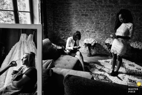 De huwelijksfotograaf van Montpellier ving dit zwart-witte artistieke spiegelbeeld van een bruid die make-up krijgt toegepast terwijl de bruidsmeisjes enkel daarna wachten