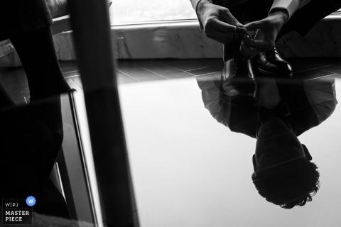 Fuzhou-Hochzeitsfotograf nahm dieses Schwarzweiss-Bild eines Bräutigams gefangen, der seine Schuhe bindet, während wir sein Gesicht in der Reflexion einer Tabelle sehen