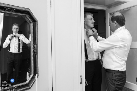 Holland wedding photographer captured this black and white image of a groom getting assistance tying his bow tie while another groomsmen straightens his in the mirror