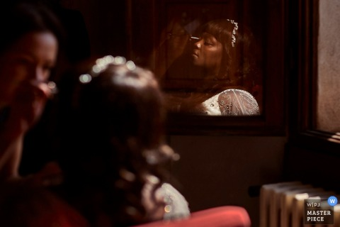 Florence wedding photographer captured this reflection image of a bride getting makeup applied before her wedding