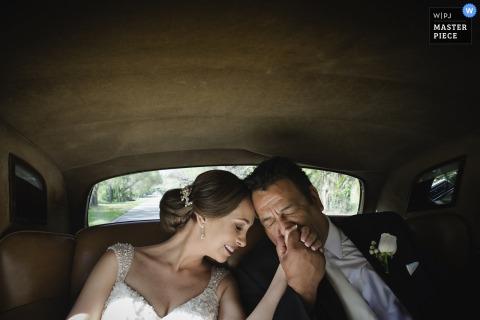 Fotograaf van het Huwelijk van Madrid ving dit beeld van een bruid en bruidegomholdingshanden terwijl wat betreft voorhoofd aan voorhoofd in de rug van een auto