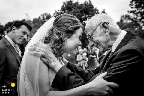 Overjissel wedding photographer captured this black and white image of the bride smiling happily at her father while her groom smiles