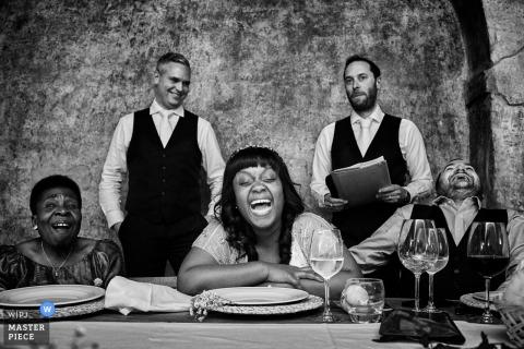 El fotógrafo de bodas de Florence capturó esta imagen en blanco y negro de una novia y un novio riéndose mientras se leen los discursos