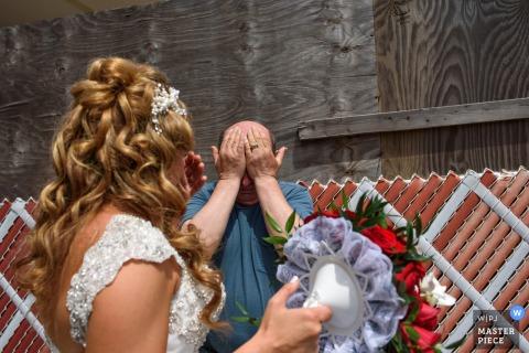 El fotógrafo de bodas de la ciudad de Nueva York capturó esta imagen exterior de una novia cubriéndose los ojos y sosteniendo un ramo rojo