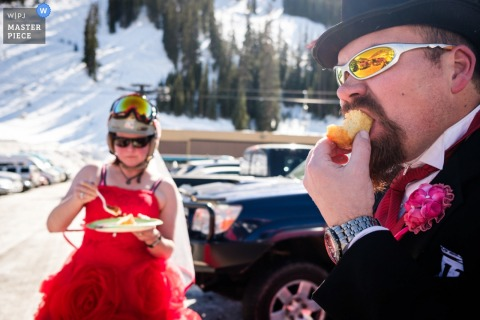 Montana wedding photographer captured this humorous photo of a bride and groom enjoying cake in ski gear in front of snow covered mountains