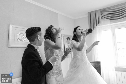 Tuscany wedding photographer captured this black and white image of a bride and bridesmaid happily drinking champagne before the ceremony