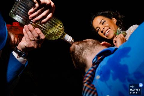Ten humorystyczny wizerunek gościa weselnego pijącego alkohol bezpośrednio z butelki z pomocą innych gości został schwytany przez fotografa ślubnego w Limie