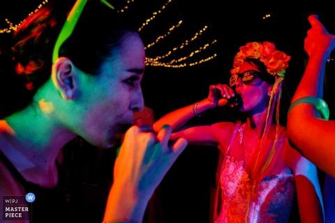 Fotograf ślubny Limy stworzył ten obraz gości weselnych korzystających z drinków na parkiecie z czerwonymi i zielonymi światłami świecącymi na nich