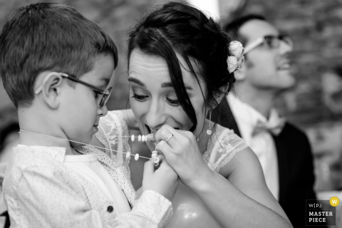 Nantes wedding photographer created this black and white picture of a bride counting the beads on the ring bearers necklace while smiling