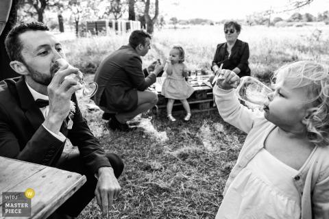De bruidsfotograaf van Montpellier creëerde dit zwart-wit beeld van een klein meisje en groomsmen die een toast delen terwijl ze aan picknicktafels op een grasveld zitten