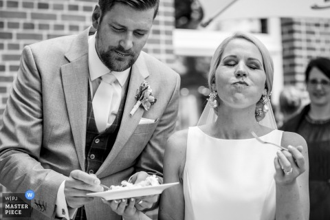 Overjissel wedding photographer captured this black and white picture of a bride and groom enjoying their wedding cake at their outdoor reception