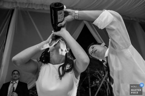 Le photographe de mariage de San Diego a capturé cette image humoristique en noir et blanc de la mariée buvant à la bouteille de champagne tandis que le marié