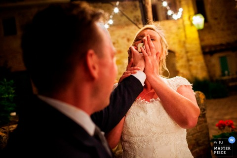 Florence wedding photographer captured this silly image of a groom smashing wedding cake into the brides face.