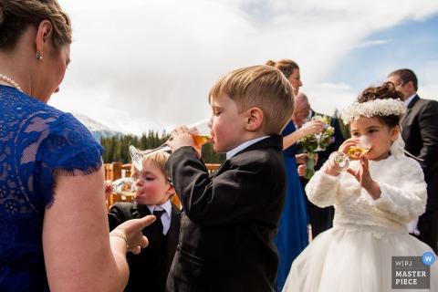 Alberta-Hochzeitsfotograf nahm dieses Bild der Kinder gefangen, die an einem Hochzeitsempfang im Freien feiern