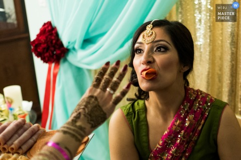 Alberta wedding photographer caught the bride getting some help eating, while protecting her makeup, before the wedding ceremony.