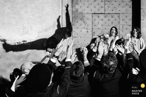 De huwelijksfotograaf van Montpellier veroverde dit humoristische zwart-witbeeld van een bruidegom schaduw op de muur als hij valt in een groep wachtende bruidsjonkers armen en bruidsmeisjes horloge in shock op de achtergrond