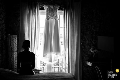 Miami wedding photographer created this black and white silhouette picture of a bride looking out a window that is draped in white curtains