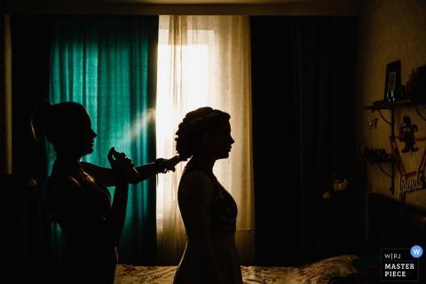 De het huwelijksprofiefoto van heilige-Petersburg ving dit silhouetbeeld van een bruid die haar haar krijgt dat voor een venster wordt gestileerd