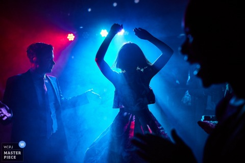 El fotógrafo de bodas de Florence creó esta imagen de un invitado de boda bailando en la pista de baile con niebla y luces azules y rojas