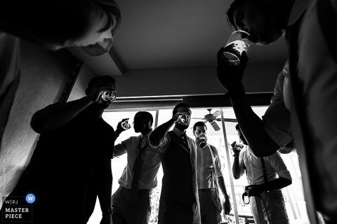 Bangkok wedding photographer captured this black and white image of groomsmen having a drink before the wedding