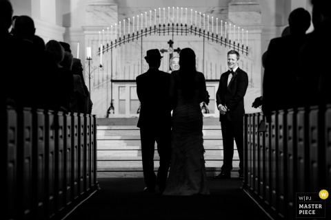 Houston wedding photographer captured this black and white image of a bride walking down the aisle in a beautiful church