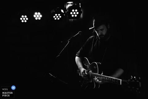 Fotograf ślubny Nowej Południowej Walii uchwycił ten obraz gitarzysty występującego pod weselem pod światłami