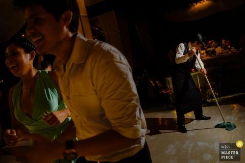 Ten obraz firmy cateringowej zmywającej parkiet, podczas gdy goście imprezowi tańczą w pobliżu, został uchwycony przez fotografa ślubnego w Limie