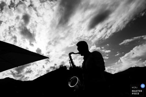 El fotógrafo de bodas de Varese capturó esta silueta en blanco y negro de un saxofonista en una recepción al aire libre