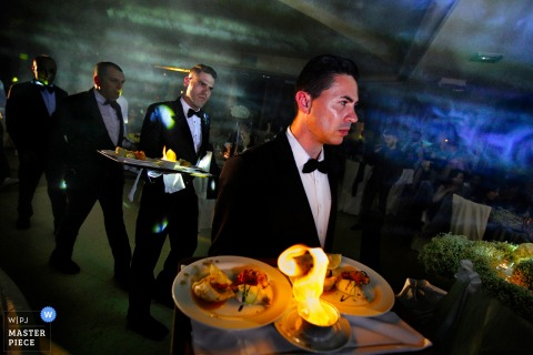 Calabria wedding photographer created this image of caterers serving wedding guests at an indoor wedding reception