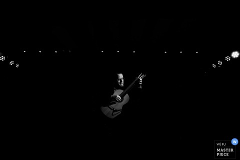 Overjissel wedding photographer captured this black and white image of a guitar player under the lights on the dance floor