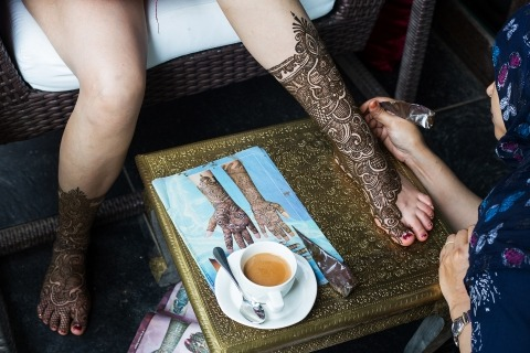 Wedding henna tattoo artist doing bride's feet. Color photo by Chetana Bhat of India.