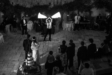 A man twirling fire at reception. Black and white photo by Raffaella Arena of Cosenza, Italy.